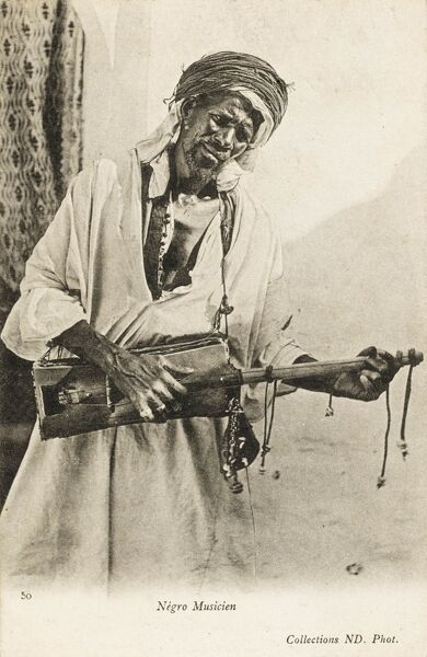 A Black Algerian musician playing a local three-stringed guitar-type instrument