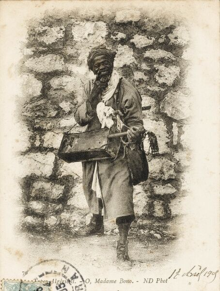 "A grinning Black Algerian Musician standing in front of a brick wall and singing a song entitled ""O, Madame Bono"", accompanying his ditty with a three-stringed traditional local guitar-type instrument. Date: circa 1905"