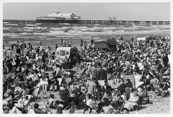 The sand is crowded with families enjoying the summer. An oyster bar and ice cream van provide refreshment