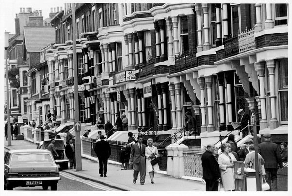 A busy scene showing holidaymakers entering and leaving typical Victorian boarding houses at Blackpool, Lancashire, England