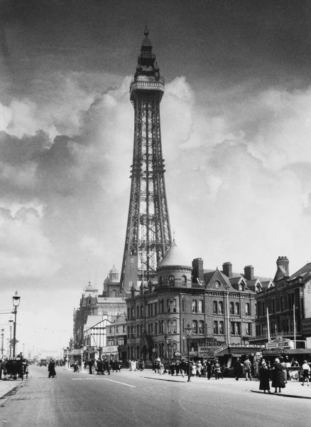 A fine view of Blackpool tower on a cloudy day, with lots of people walking, but hardly any traffic at all