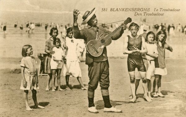 Blankenberghe, Belgium - a beach troubador, thoroughly entertaining a group of children in their bathing costumes