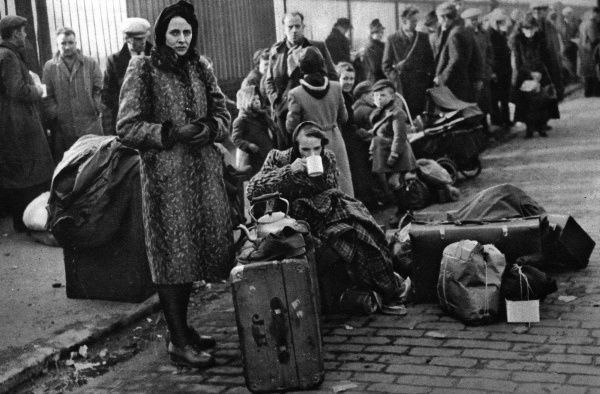 Women and children waiting on a street with the few possesions left to them after a night's bombing on Clydeside. Date: 1941