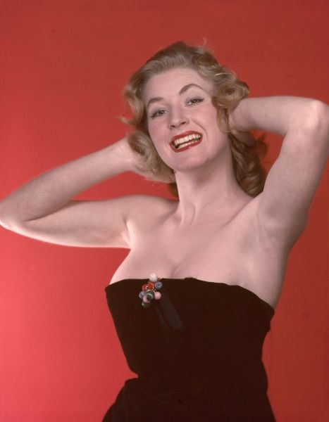 Fifties blonde bombshell, posed with her arms behind her head, wears some strategically arranged black velvet which looks like it may fall off at any moment