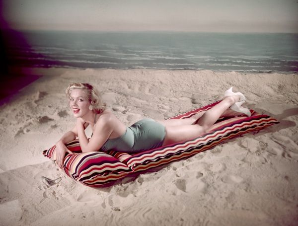 Pretty blonde bathing beauty, wearing white court shoes & a pale blue, halter-neck one- piece bathing costume, poses on an inflatable lilo on a sandy beach