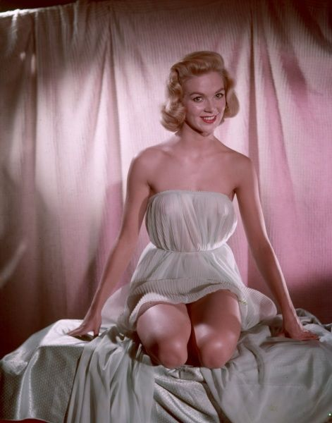 Fifties blonde bombshell, in a strapless accordian pleated chemise, kneels demurely on a chiffon sheet