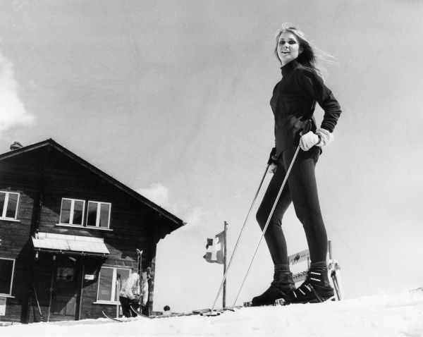 A blonde model on skiis, posing outside a chalet. Date: 1960s