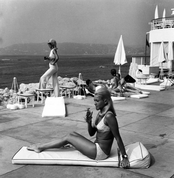 Two trendy blondes on holiday, one relaxing on a sunbed and the other looking out to sea, both having drinks on the hotel patio; Juan les Pins, France. Date: 1960s