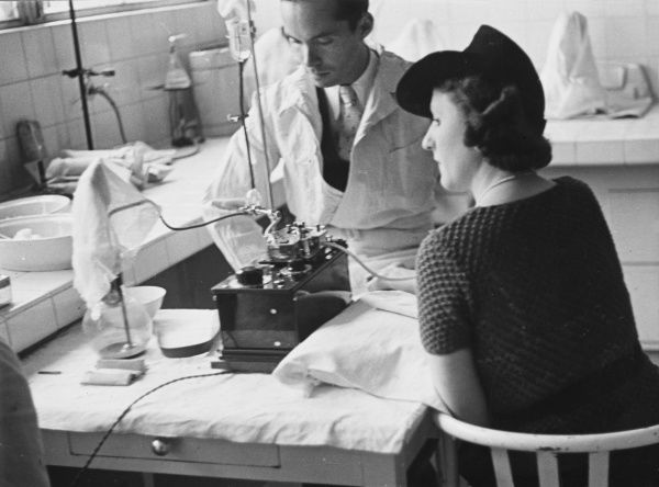 A French blood donor curiously watches her blood running into the receptable provided during World War II