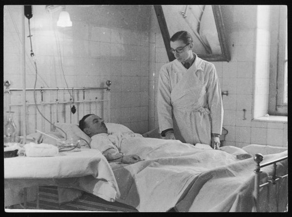 A hospital patient in his bed receiving a blood transfusion from an ampule of stored blood, seen on the top left hand side of the photograph