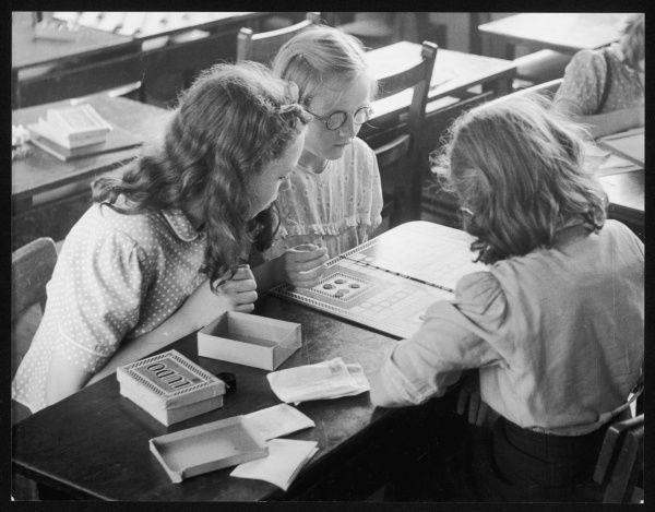 A group of young schoolgirls playing a board game