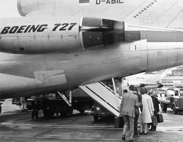 Passengers at London (Heathrow) airport boarding a Boeing 727 (Lufthansa) on the runway. Date: 1960s