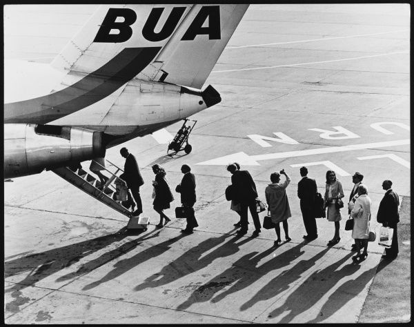 Passengers boarding a British United Airways (BUA) aeroplane on one of the runways at London Gatwick Airport, Surrey, England