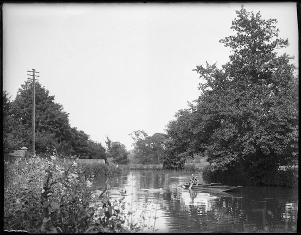 A boy in a rowing boat on the River Wey, Godalming, Surrey, England