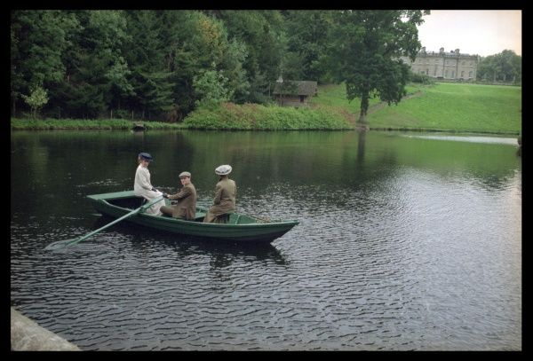 Two Edwardian ladies and a boy enjoy themselves in a rowing boat on a boating lake