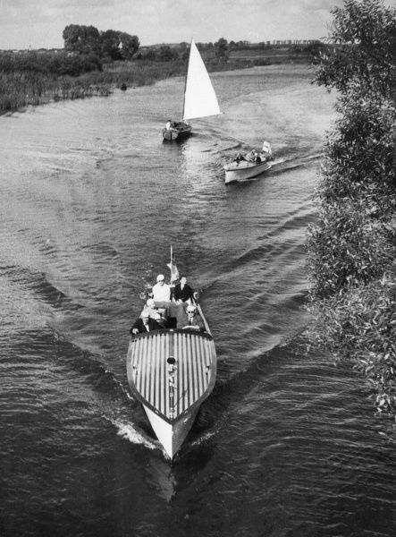Boating for pleasure : Power boats and a yacht, possibly on the Norfolk Broads, England. Date: 1930s
