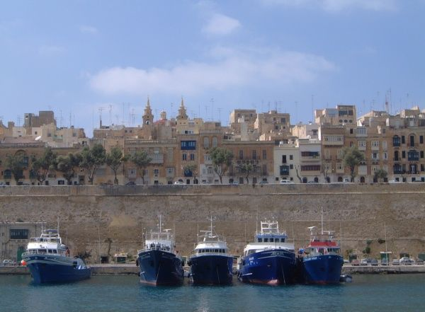 Boats moored beneath the walls on the eastern side of the Valletta peninsula, viewed from the Grand Harbour