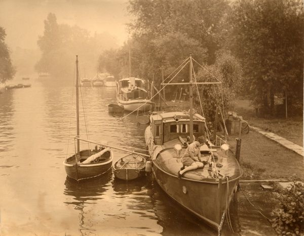 A tranquil view of the Thames, looking towards Richmond with boats moored at a jetty and a woman sitting on the deck of the boat in the foreground