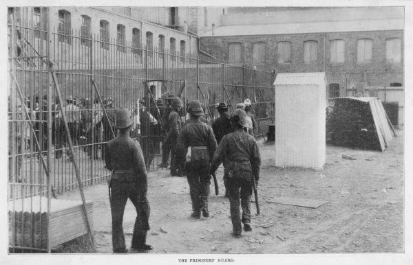 Boer prisoners escorted inside the prison by armed guard