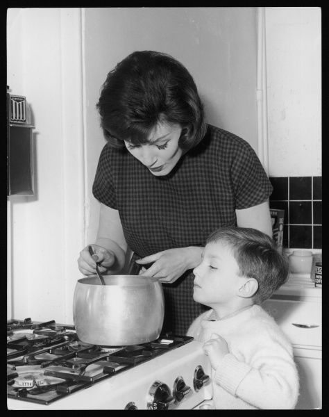 A young mother stirs a saucepan of soup on the cooker, watched by her little boy!