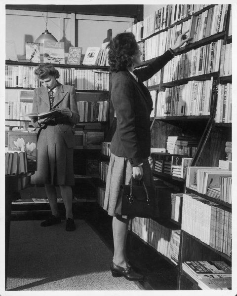 "Two women, both wearing box pleated skirts, browse around a bookshop, which is selling the latest books, such as Godfrey Winn's ""Scrapbook of Victory&quot"