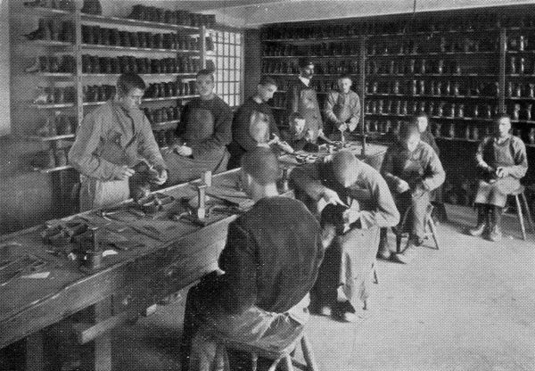 Boot-making workshop at the East Harling, Norfolk, branch of the National Institutions for Persons Requiring Care and Control, an organisation privately run by the Rev Harold Burden to house 'feeble minded' children. The site, at Kenninghall