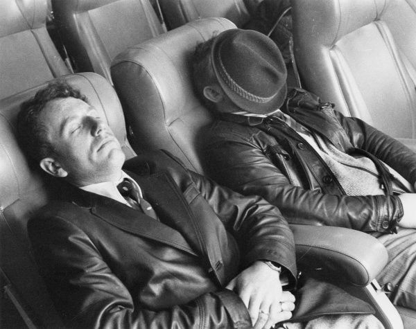 Two men in leather jackets, one of them with his hat over his face, take a nap on a cross Channnel ferry, perhaps having had too much booze on their cruise!