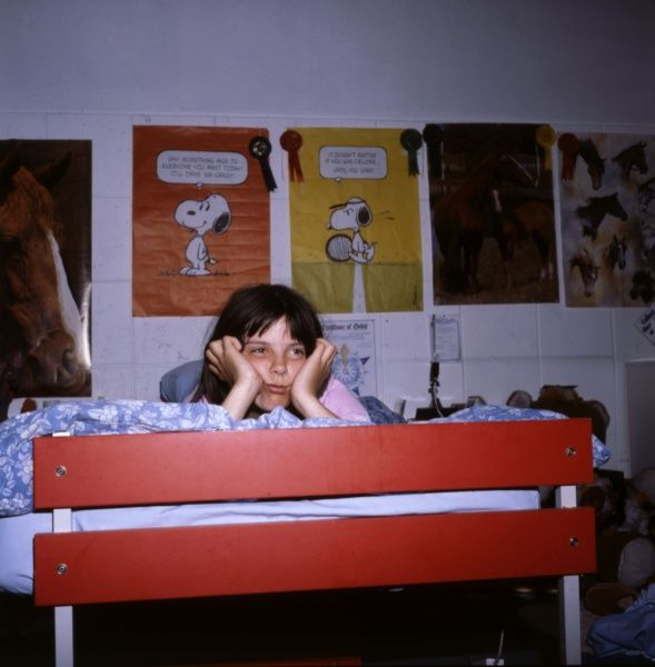 A bored teenage girl, sulking in her bedroom, dreaming of being grown up and having fun, her 'Snoopy' posters behind her. Date: 1979