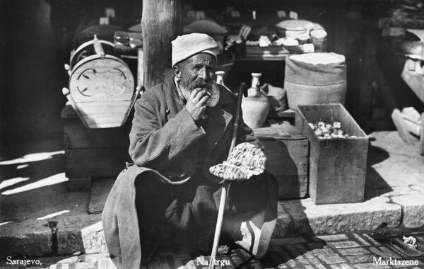 An old Bosnian man tucks into his lunch in a Sarajevo Market. He appears to be eating some form of folded flatbread