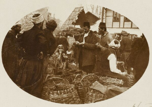 Traders at a street market in Bosnia Herzegovina. Selling wares from large wicker baskets