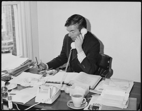 Working lunch - a businessman answers the telephone in his office, with his sandwich and cup of tea on his desk