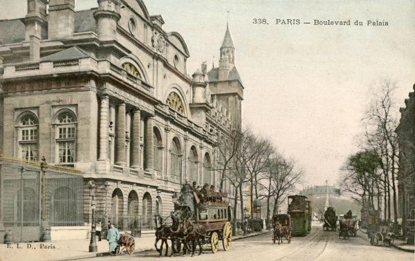 A horse bus, an electric tram, other horse-drawn vehicles, and a hand-cart, cross the Ile de la Cite past the Palais de Justice ; a traditional pissoir is just visible