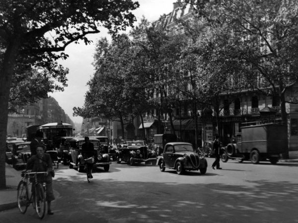 Cars and cyclists on the busy Boulevard Haussmann, Paris, France. Date: 1930s