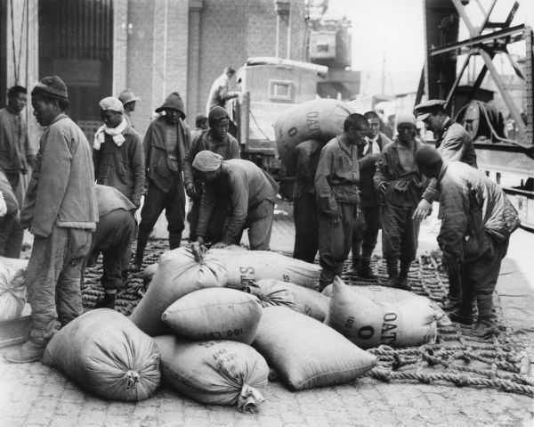 Under the instruction of a British officer, Chinese labourers load sacks of oats at Boulogne Docks