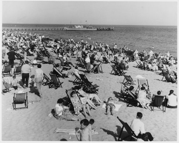 A crowded beach scene at Bournemouth. People sunbathe in deckchairs and swim in the sea
