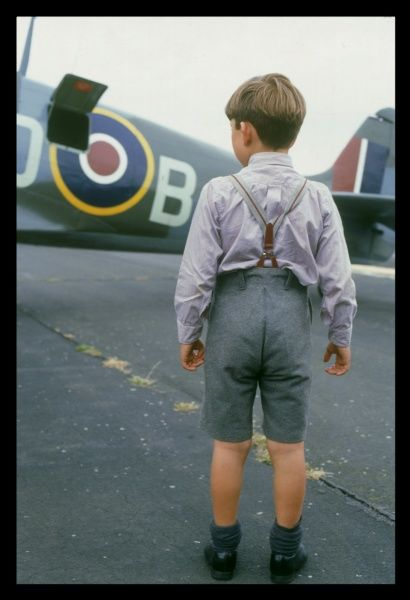 Spitfire Summer: A little boy wearing shorts and braces admires a Spitfire on the runway at Biggin Hill, Kent, England