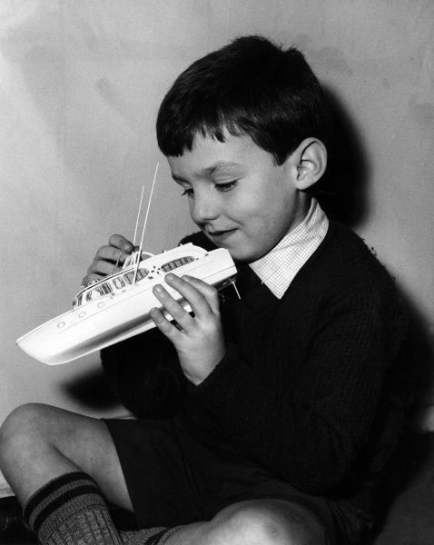A happy little boy playing with his model power boat. Date: mid 1950s