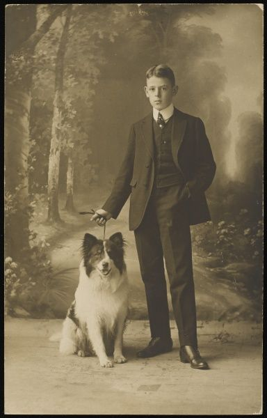 A young boy in a smart suit and starched collar poses for a studio portrait with his dog, a collie, on a lead
