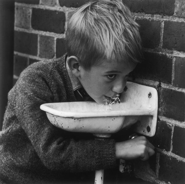 A schoolboy drinks from a water fountain