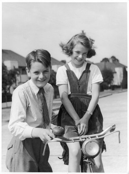 A boy in his school uniform and a girl, wearing a corduroy pinafore dress and seated on a bicycle, pose for the camera