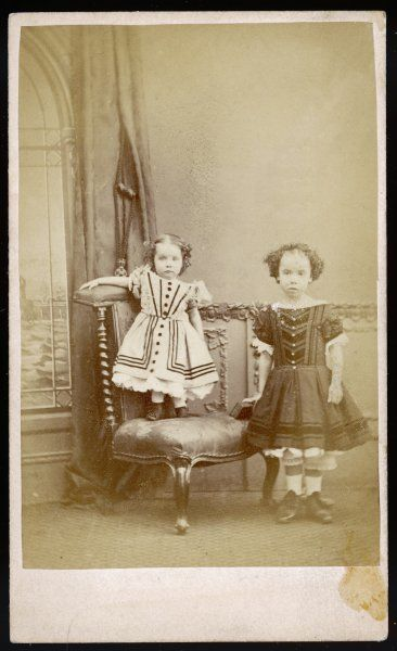 Brother & sister wear frocks that are cut low off the shoulder, lace petticoats & trousers. Frocks have simulated stomacher bodices, buttons & applied ribbon trim