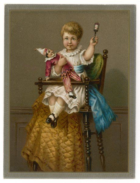 A boy in a high chair, with his rattle and a Punch doll