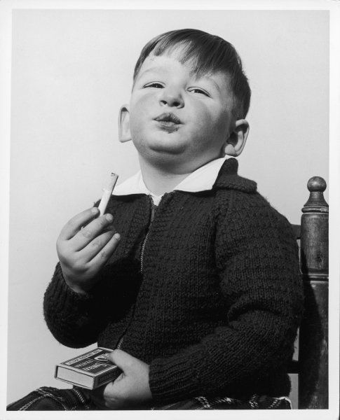 A young boy pretends to smoke and feels very grown up