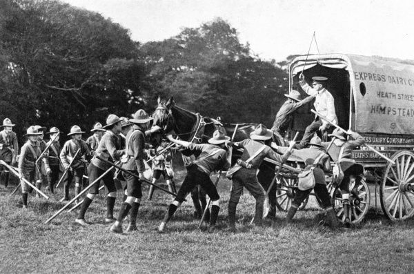 A group of boy scouts holding up a provision van of the Express Dairy Company, on Hampstead Heath, London. Date: 1910