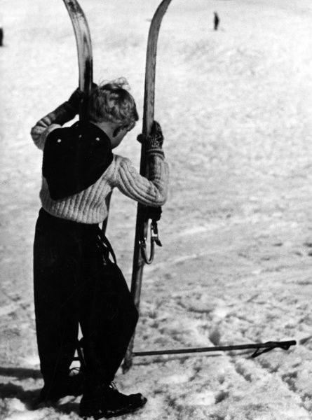A little boy holding up a large pair of skis. Date: 1930s