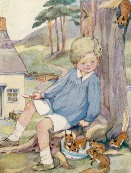 A small blond boy wearing a smock and shorts sits under a tree watching a group of inquisitive squirrels feed from a bowl