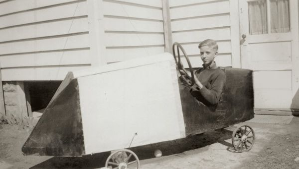 A boy at the wheel of a rocket-shaped toy pedal car, posing outside his wooden boarded house