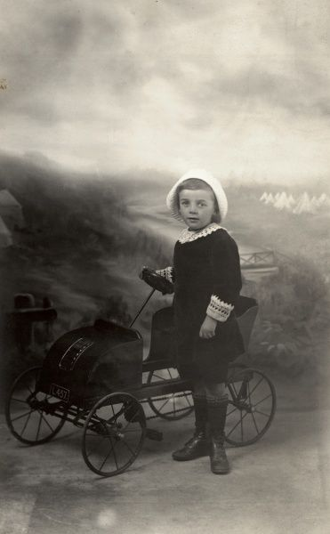 A little boy wearing his Sunday best Little Lord Fauntleroy outfit complete with lace collar and cuffs, counterbalances his effeminate outfit with a masculine pedal car which would be the pride of any Edwardian petrol head