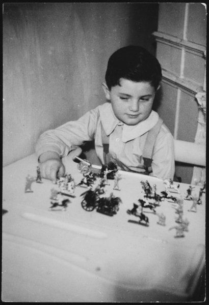 A very contented young boy playing with the battlefield of toy soldiers he has created on a table at home