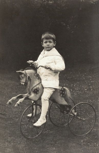 A very solemn and serious looking little boy, trussed up in a white sailor suit sits astride a toy horse which is fixed to three wheels - a sort of horcycle?